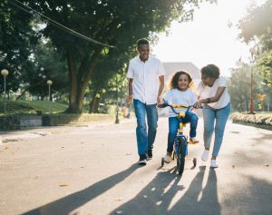 Parents helping a child ride a bike. Give your child support through child counseling and play therapy. Roswell, GA 30076