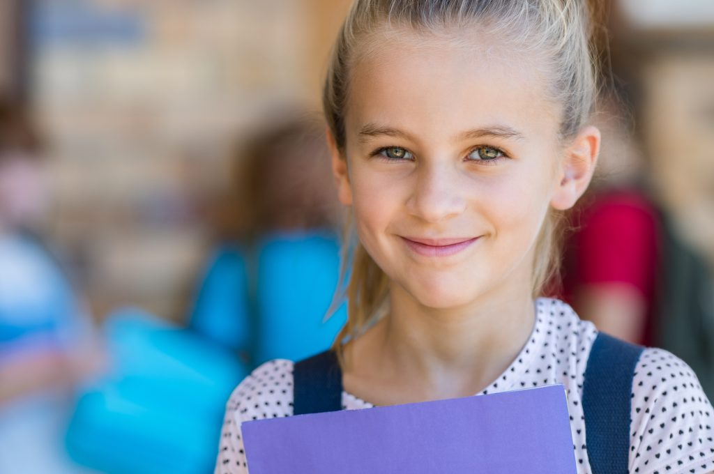 An elementary age girl holding a folder smiles while in front of other students at school. Child counseling and play therapy helps children overcome obstacles and grow to their full potential with counseling for children in Roswell, GA. 30076.