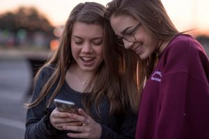 A couple of happy smiling teenage girls look at a cellphone with each other. Teenagers face a lot of stressors, including the more demanding academic expectations in school, coping with new and confusing emotions and feelings and engaging in new and changing relationships. Teen counseling can help teens process emotions and manage the stress that comes with this stage of life with the help of a teen therapist in Roswell, GA. 30076