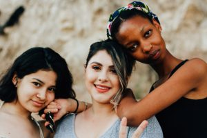 Three teenage girls lean on each other's shoulders by a rock outcropping. Counseling for teens can help teenage girls work through changing relationships and re-engage with family and friends with the help of a counselor for teens in Roswell, GA. 30076
