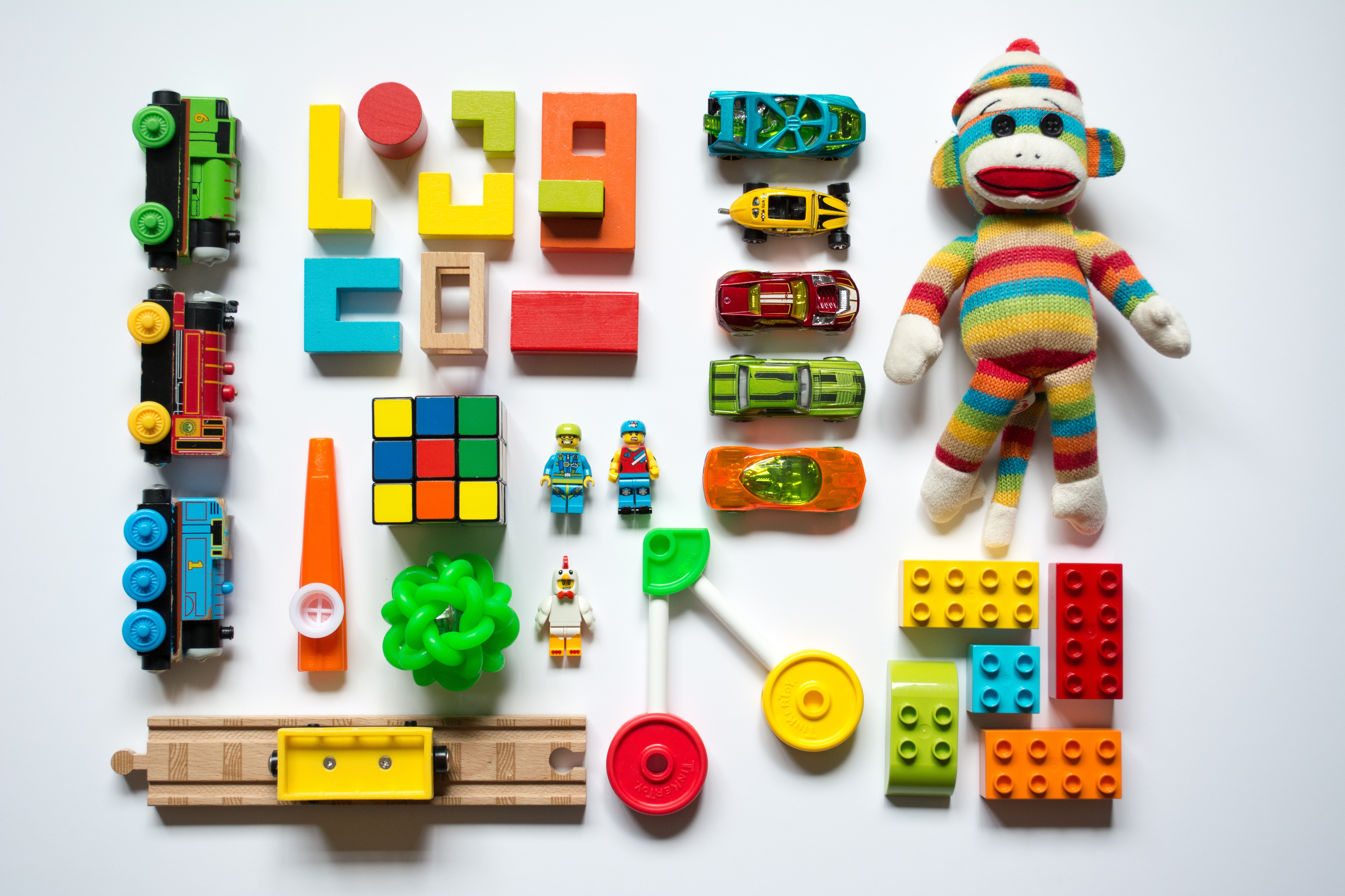 Toy trains, wooden blocks, toy cars, legos and a rainbow colored stuffed monkey lay on a white background in organized columns. Play therapy for children allows children to recognize emotions and is beneficial for children who have experienced trauma, low-self esteem or meltdowns. Play therapy for kids is available with a skilled child counselor near Atlanta in Roswell, GA 30076.