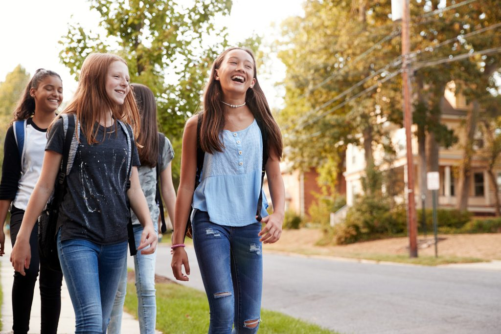 Four teenage girls walking smiling and talking | Teen Counseling for Anxiety and Depression | Roswell, GA near Altanta, GA 30076.