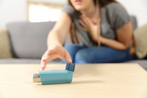 Woman with hand at her neck reaching for an inhaler in distress | chronic illness counseling | 30076