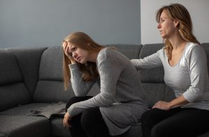 Sad teen being comforted by mother on gray couch | Positive Discipline & Parenting Support | Wellview Counseling 30076