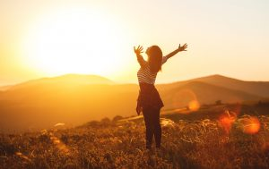 Happy woman standing in sunrise with arms out open wide after attending trauma therapy and getting treatment for PTSD in Roswell, GA.