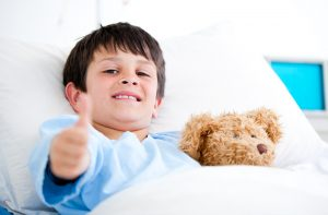 Little Boy Hugging A Teddy Bear Lying In A Hospital Bed in Atlanta, GA after talking to a counselor. 30076