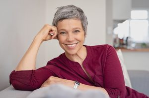 Photo of middle aged woman in burgundy top smiling with head on her hand after receiving counseling for chronic illness | Wellview Counseling | 30076