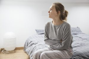 Young woman wearing grey sweats sitting on bed with her hands folded over her stomach looking sad | chronic illness counseling | Wellview Counseling | 30076
