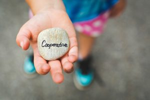 Picture of young child holding a rock with the word cooperative on it | Positive Discipline training & Parent Support | Wellview Counseling | Roswell, GA 30076