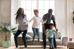 Happy African American family dancing on couch after receiving positive discipline parent education at Wellview Counseling in Atlanta, GA 30076