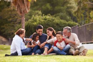 multi-generational hispanic family sitting in a park | family therapy | Wellview Counseling | 30076
