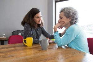 Photo of young woman comforting mother while drinking coffee at the table | family therapy | Wellview Counseling | 30076
