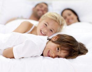 Happy family resting in bed together | Counseling in Atlanta Area | Therapy in Rosewell, GA | 30076