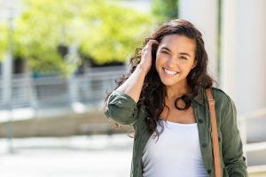 Hispanic woman smiling at the camera outside feeling relieved after trauma treatment with a trauma therapist | Trauma & PTSD therapy in Atlanta 30076
