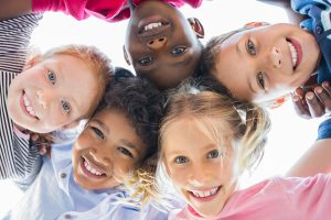 Photo of a group of multiethnic children smiling at the camera in a group. These children are leaning new social skills for kids during group therapy in Roswell, GA near Atlanta at Wellview Counseling 30076