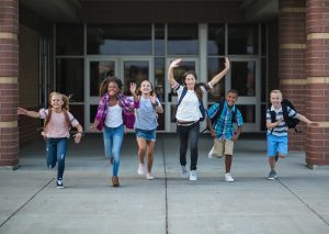 Photo of happy pre teens running excitedly after school. Some of these children have benefited from social skills group for kids and autism social skills at Wellview Counseling in the Roswell, GA near Atlanta 30076