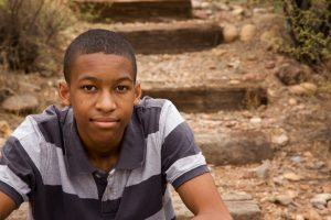 Handsome young african american boy sitting on steps outside before going to teen counseling with a teen therapist at Wellview Counseling in the Atlanta Area 30076