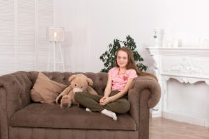preteen girl sits on the couch looking very happy after teen counseling with a teen therapist in Rosewell GA at Wellview Counseling 30076