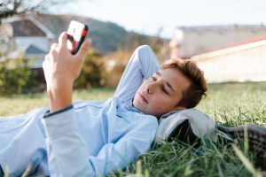 teen boy lays in the grass on his cell phone chatting with his friends on FaceTime. He also receives teen counseling via online therapy in Georgia with Wellview Therapy