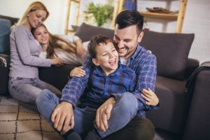 happy family plays at home during the coronavirus pandemic. They attend family therapy with a wellview counselor during online therapy in Georgia. 33076