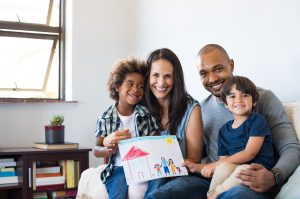 Proud mixed-race family shows sits on the couch holding a photo of the family drawn by the kids. They received family therapy from a wellveiw therapist during online therapy in Georgia.