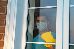 man does chores and washes a window in a mask during COVID. He gets online therapy in Georgia with Wellview Counseling