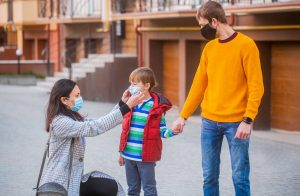 family wearing masks outdoors. Mother adjust her sons mask. Therapist in Roswell, GA shares tips on how to handle awkward social situations during the COVID-19 crisis