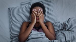 Black woman with hands over face in bed representing insomnia and sleep issues. Get counseling in Roswell, GA at Wellview Counseling to help with sleep disturbances
