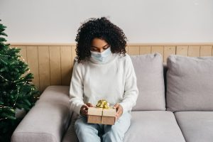 woman opens a present while wearing a mask at holiday festivities during COVID-19. She goes to Wellview counseling for online therapy in Georgia