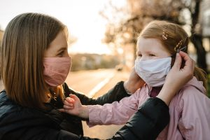 mother puts a mask on her young daughter who looks happy. She was worried about her child's socialization during the pandemic, but a child therapist in Atlanta, GA at wellview counseling offered her reassurance.