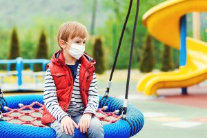 sad boy on a spider swing at the park wearing a mask during the pandemic. His parents are worried about his socialization and development but Ashley Bobo a child therapist in Atlanta, GA says that's not necessary