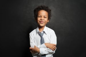 Happy young Black boy in a tie smiles in a school photo. He learned social skills that boosted his confidence and resiliency during child counseling in Roswell, GA