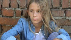 Unhappy preteen girl looks away from the camera after being bullied at school. She gets support from a child therapist during child counseling in Roswell, GA at Wellview Counseling