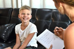 Child meeting with a child therapist in Roswell, GA. His mother learned tips for talking to her son about child counseling from Wellview Counseling.