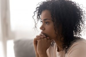 Black woman with anxiety sits at home on her sofa looking upset. She is not doing the things she used to enjoy. She represents someone participating in anxiety treatment with an online therapist in Roswell, GA with Wellview Counseling