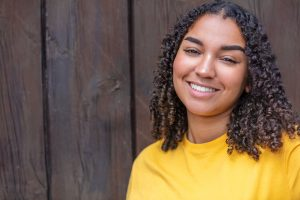 Smiling african american teen girl in a yellow shirt representing the happy feelings adolescents have after teen cousneling
