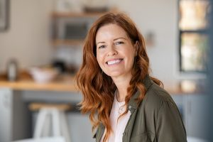 Woman with red hair sits at her kitchen table and smiles. She represents someone benefiting from working with an anxiety therapist during anxiety treatment in Roswell, GA