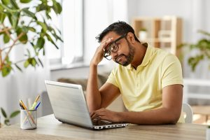 Indian man with anxiety sits in front of his laptop with his hand on his forehead due to a headache. He represents someone who benefits from anxiety treatment with an online anxiety therapist in Roswell, GA.