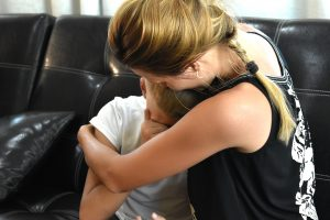 mother hugging her upset son on the sofa. He gets help from a child therapist offering child counseling in Roswell, GA at Wellview Counseling 30076