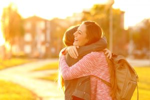 A teen smiles as they hug their friend in the evening sun. This could represent the benefits of teen counseling in Roswell, GA. Contact an online anxiety therapist in Roswell, GA for support. A teen therapist would be happy to support you!
