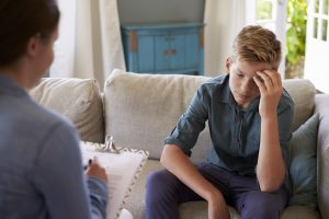 A teen sits on the sofa with an upset look on his face as a person with a clipboard writes across from them. This could represent teen counseling in Roswell, GA. You can learn more from an online anxiety therapist in Roswell, GA. Contact an anxiety therapist for support today!