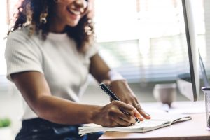 A woman smiles as she writes in a notebook. This could represent journaling to calm anxiety. Teen counseling in Roswell, GA can provide support. Contact an online anxiety therapist for support today!