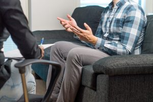 A person gestures with their hands as they speak to a person holding a clipboard. A young adult therapist in Roswell, GA can offer support with life transitions therapy and other services.