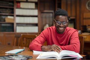 Black male student reads a textbook in the library. This represents the benefits of managing your stress as a new college student. Get more tips from a therapist who offers young adults therapy in Roswell, GA