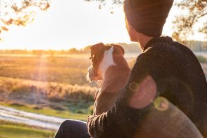 A young adult sits with their dog as they watch the sunset. This could represent the support that young adult therapy in Roswell, GA can provide. Contact a young adult therapist to learn more about life transitions therapy and other services today!
