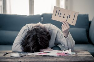 """A woman sits with her head down on a desk as she holds a """"help!"""" sign. Young adult therapy in Roswell, GA can offer support with major life transitions. Contact a young adult therapist in Roswell, GA to learn more."""
