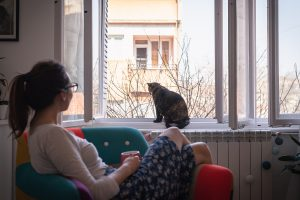 A young woman sits with a drink as she watches her cat at an open window. Contact a young adult therapist in Roswell, GA for support with life transitions therapy and other services.