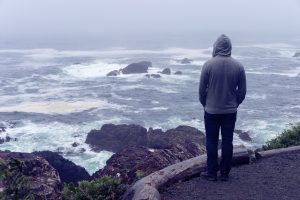 A person stands overlooking a rocky shore. Young adult therapy in Roswell, GA can offer support for feelings of isolation. Contact a young adult therapist in Roswell, GA for support with life transitions therapy in Roswell, GA today.